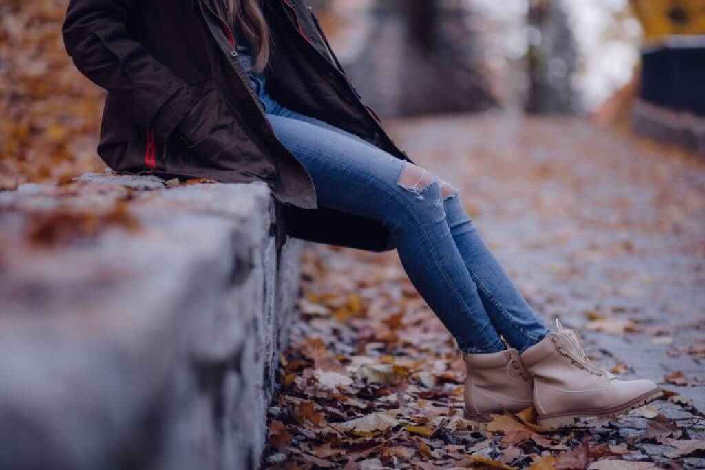 a girl wearing ripped jeans and booties sits outside during the fall