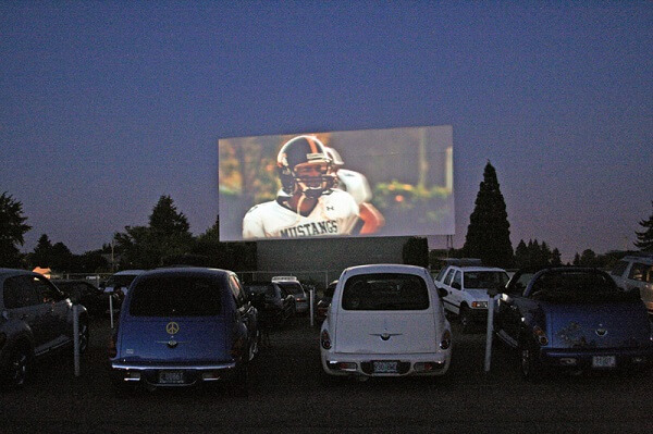 two cars sit at a drive in movie in Walla Walla valley