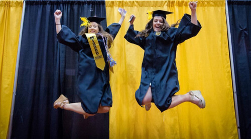 Mizzou graduates jump in the air in their caps and gowns.