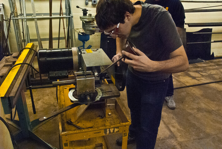 student working on a solar car in a quirky iowa club