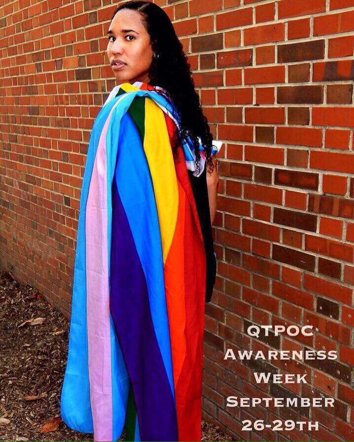 Ellie Gaustria, president of QTPOCU, poses with the gay pride and transgender pride flags draped over her shoulder.