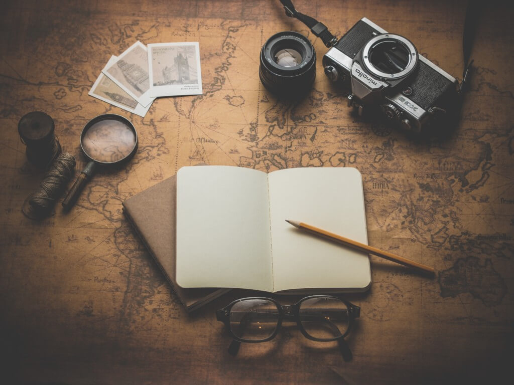 a notebook, glasses and photos from journalism minors