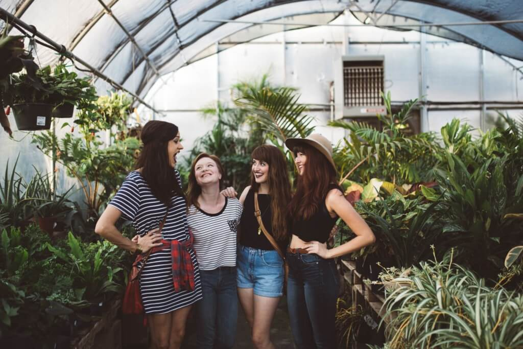 four girl friends laughing in a green house