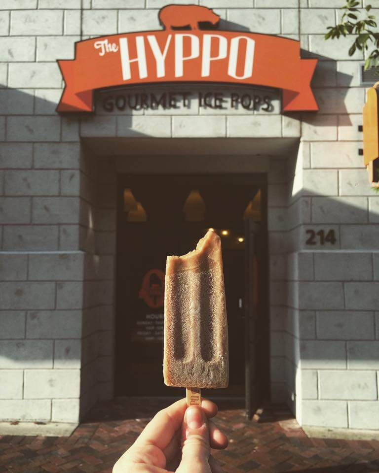 A hand holds up a Hyppo popsicle in front of the store's front door in Gainesville.