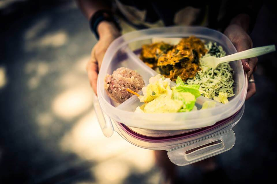 Tupperware filled with Krishna Lunch in Gainesville, complete with vegetables, salad, and a scoop of halava.