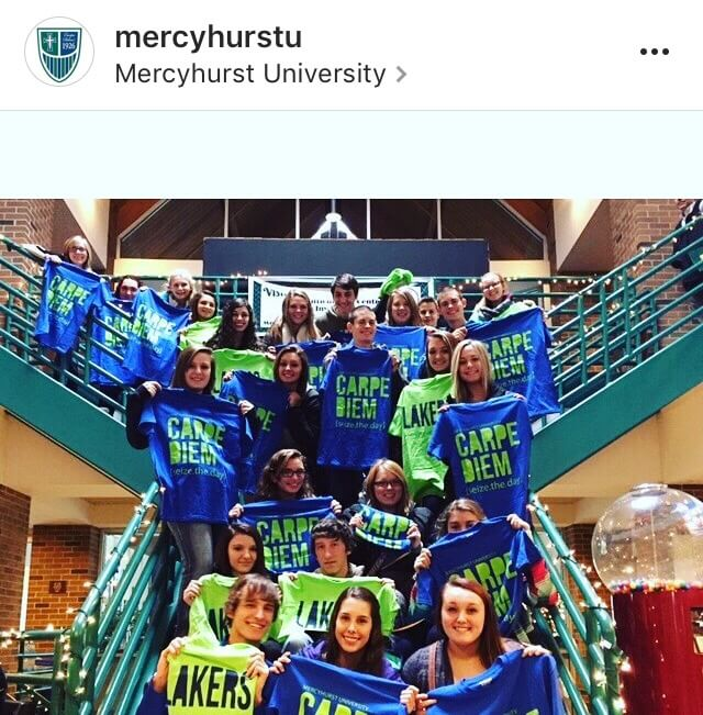 Mercyhurst students hold up school spirit shirts