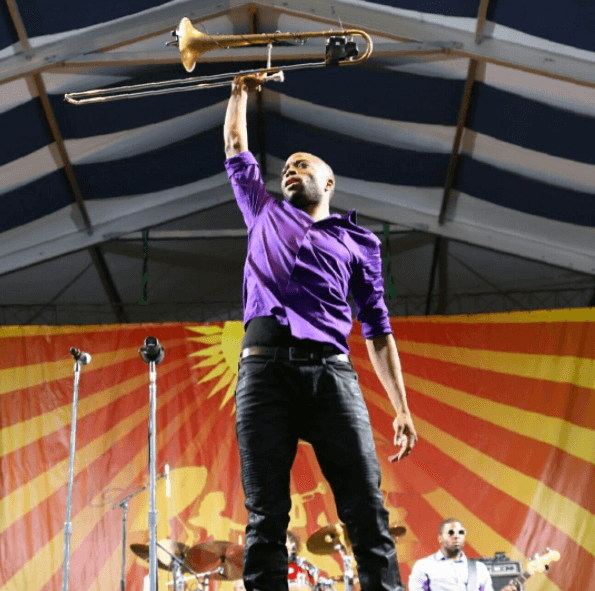 A musician holds up his trombone at Jazz Fest in NOLA.