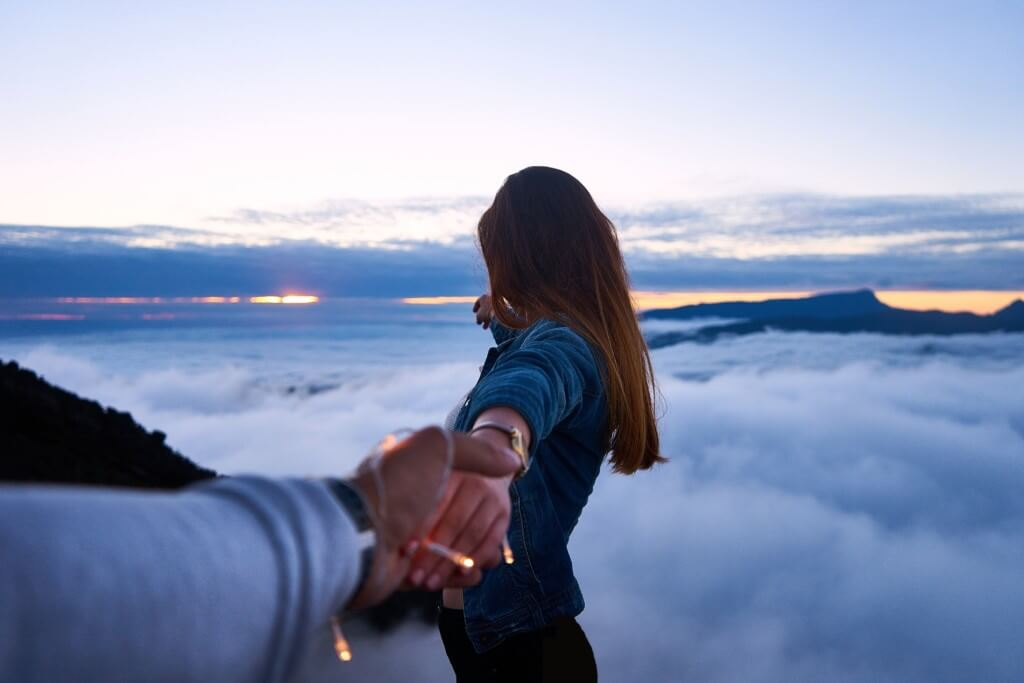 long-distance relationship couple holding hands looking at clouds