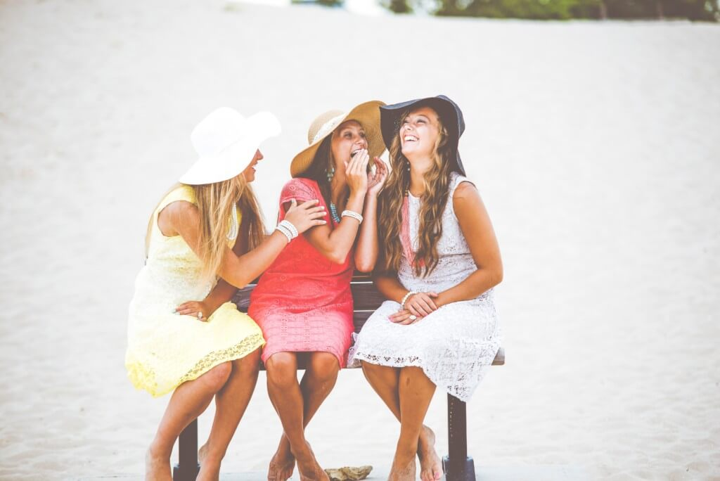 sorority girls in sundresses and hats sitting and laughing together
