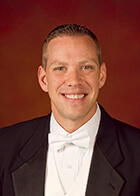 This picture shows Prof. Shawn Vondran from Northwestern Bienen School of Music smiling in a black suit and white bowtie against a red background.