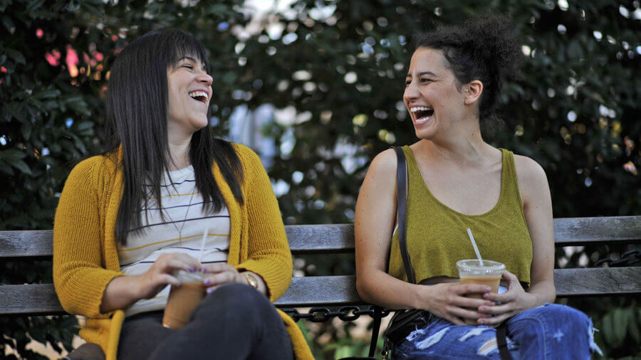 Actresses from Broad City sit on a bench laughing.