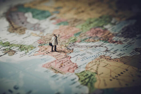 Figurine of man standing on a world map, ready to take on the world.