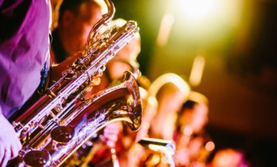Florescent lighting with a strong purple focus on Saxaphone players.
