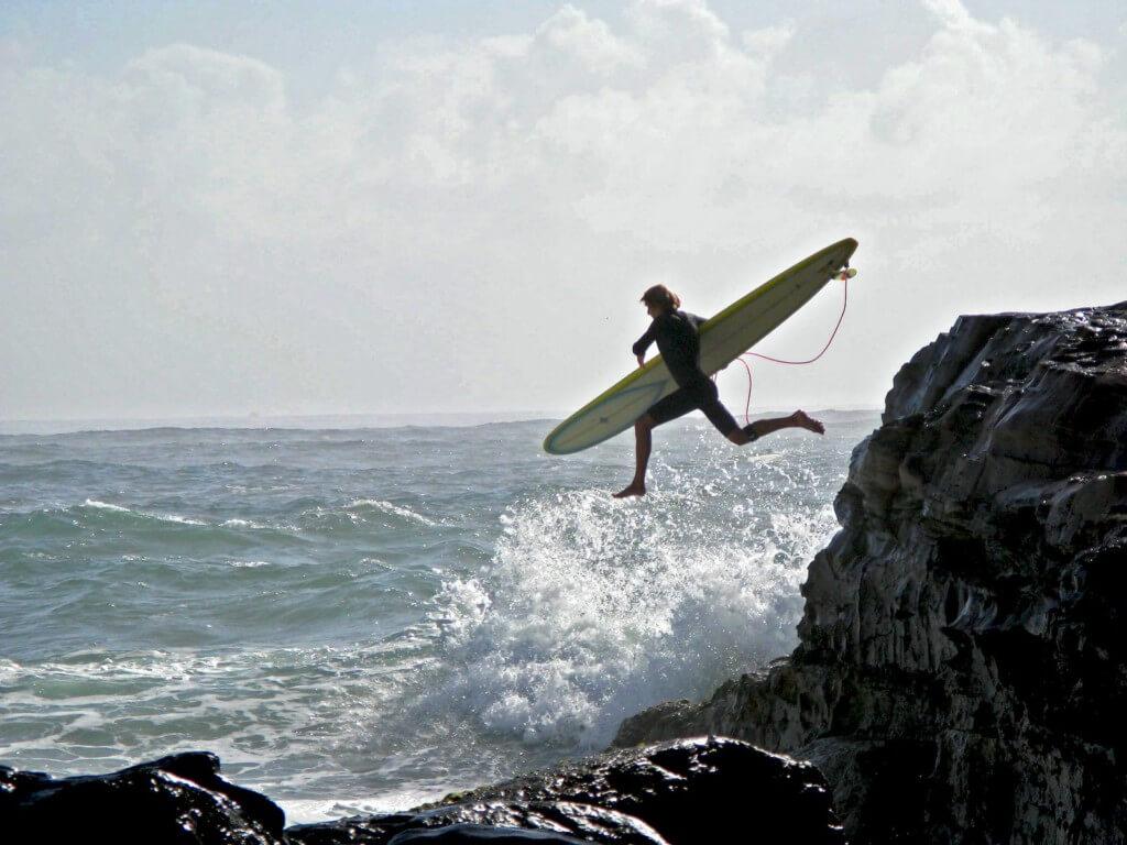 surfer diving into ocean