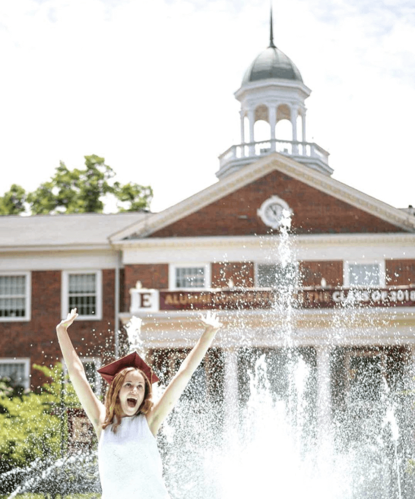 elon university grad in front of fountain