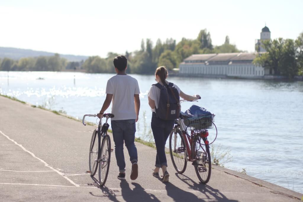 boy and girl walk their bicycles together along a riverbank