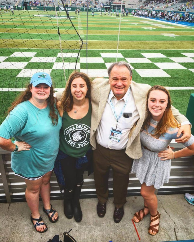 three girls and Tulane president Mike Fitts at a Tulane football game