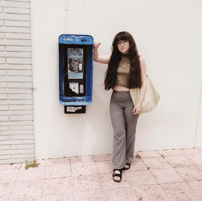 Tulane student in front of a phone booth