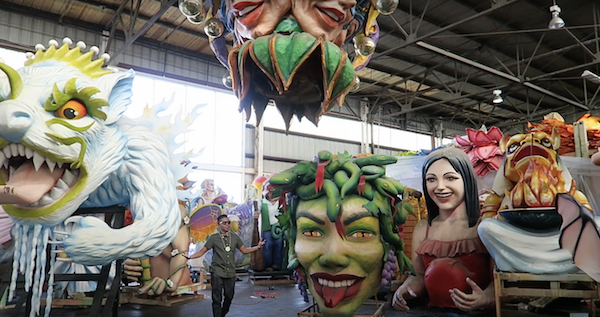 Man standing next to floats at Mardi gras world New Orleans