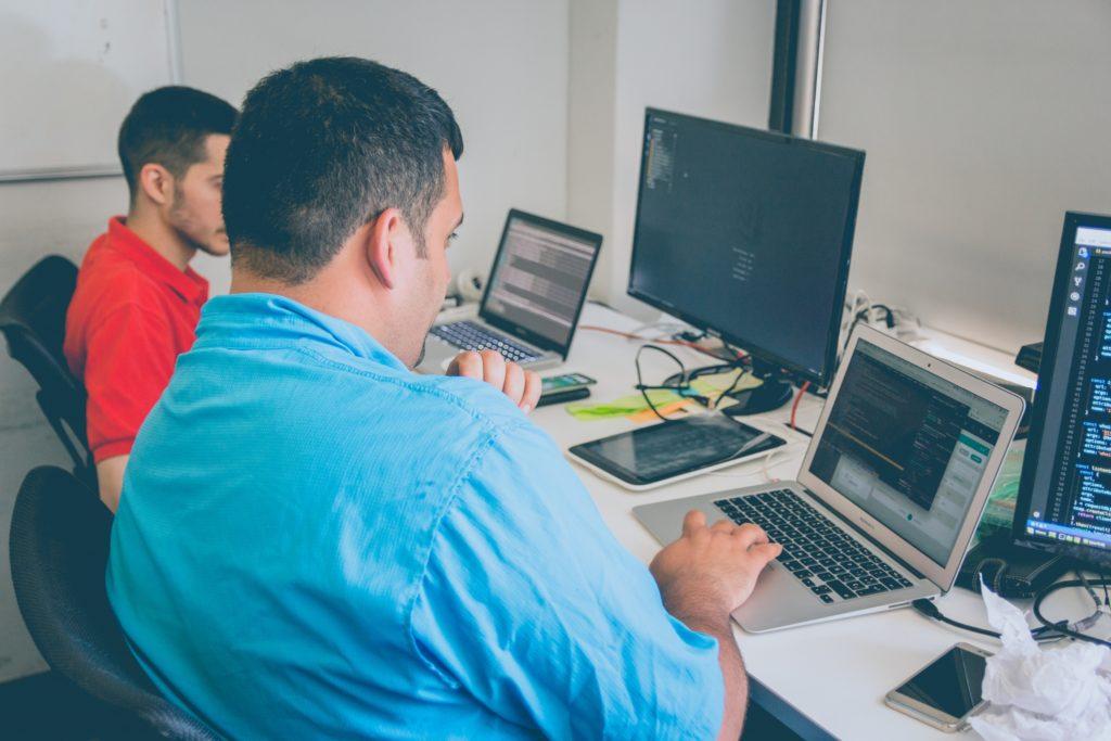 men looking at laptop interpersonal skills