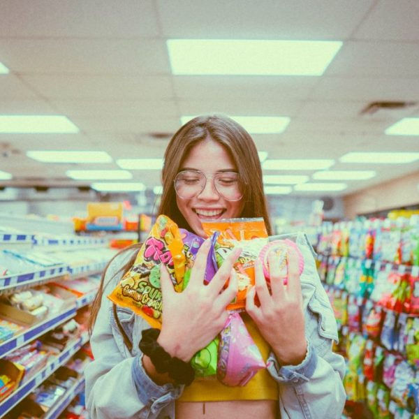 girl holding bags of candy smiling