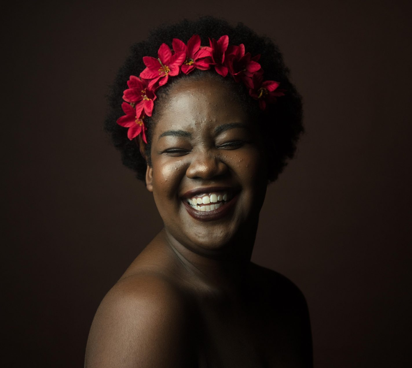 woman with red flowers in hair laughing close up period panties