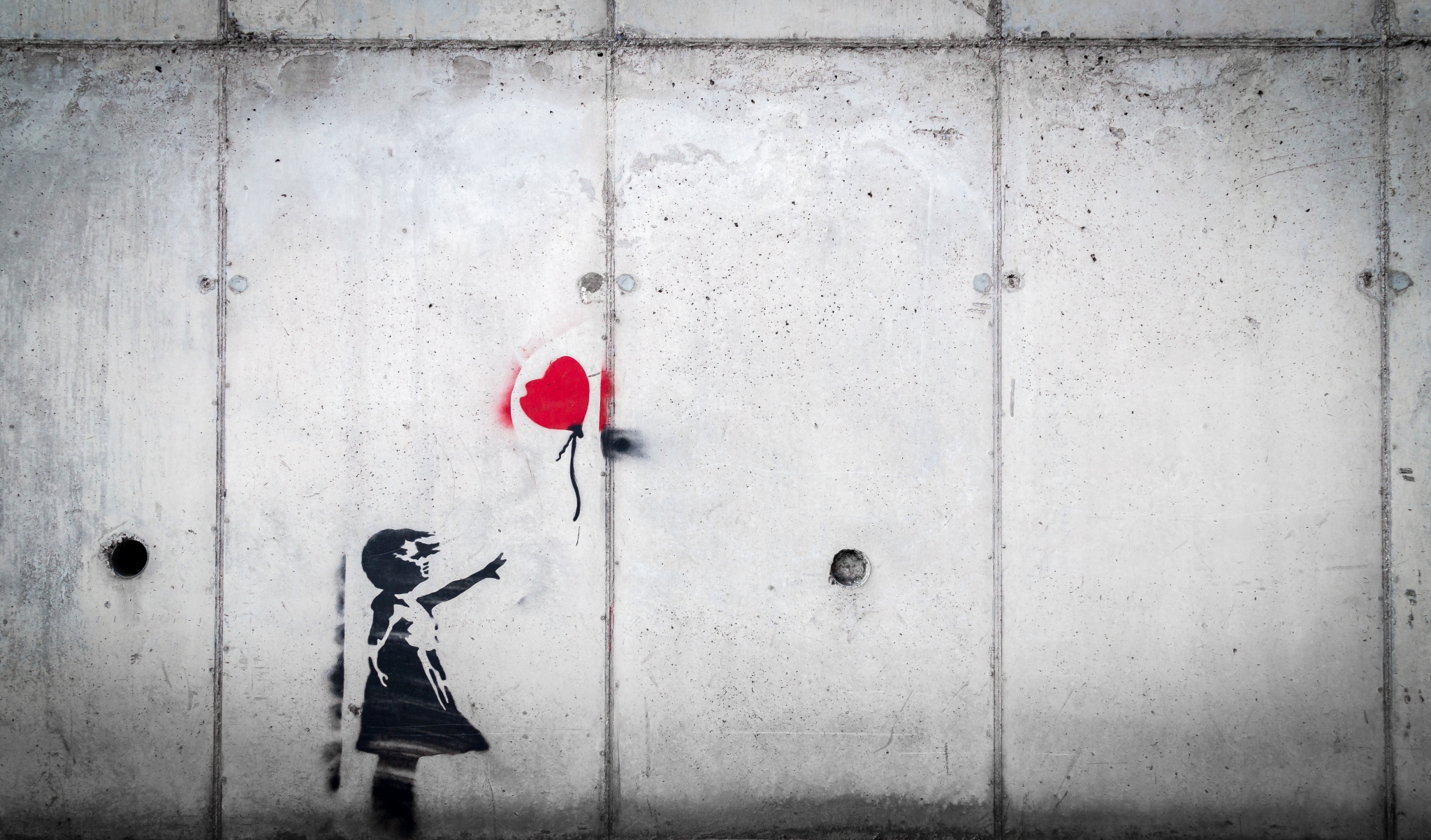 girl reaching for red heart balloon