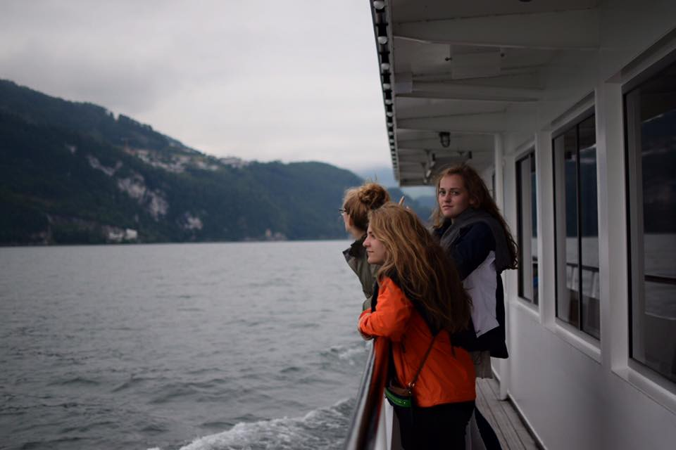 girls on ferry boat with mountains best places to visit in europe