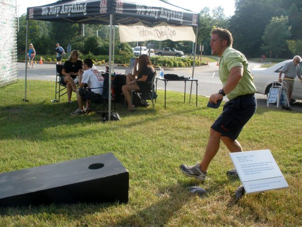 man tossing bean bag into corn hole game