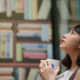 Woman looking up in front of book shelves
