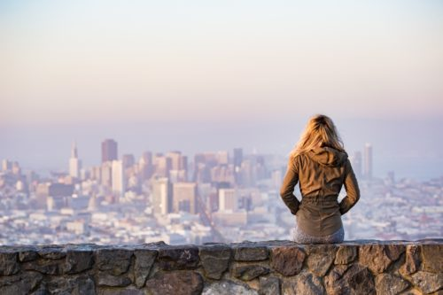 Girl sitting in front of city-scape