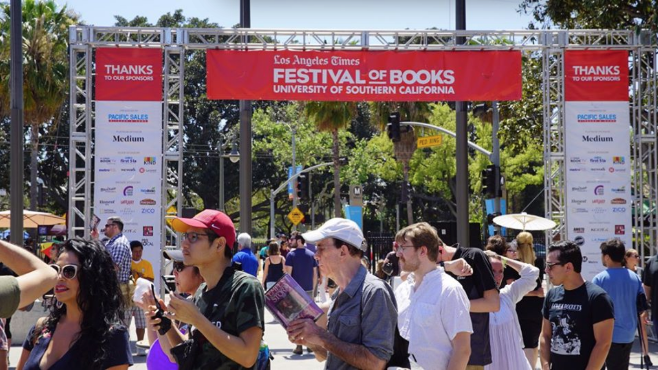Civilians in line at the L.A Times Festival of Books with a banner in the background.