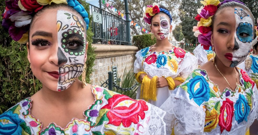 3 girsl dreseed in traditional mexican clothing and facepaint pose in front of the camera for a picture.
