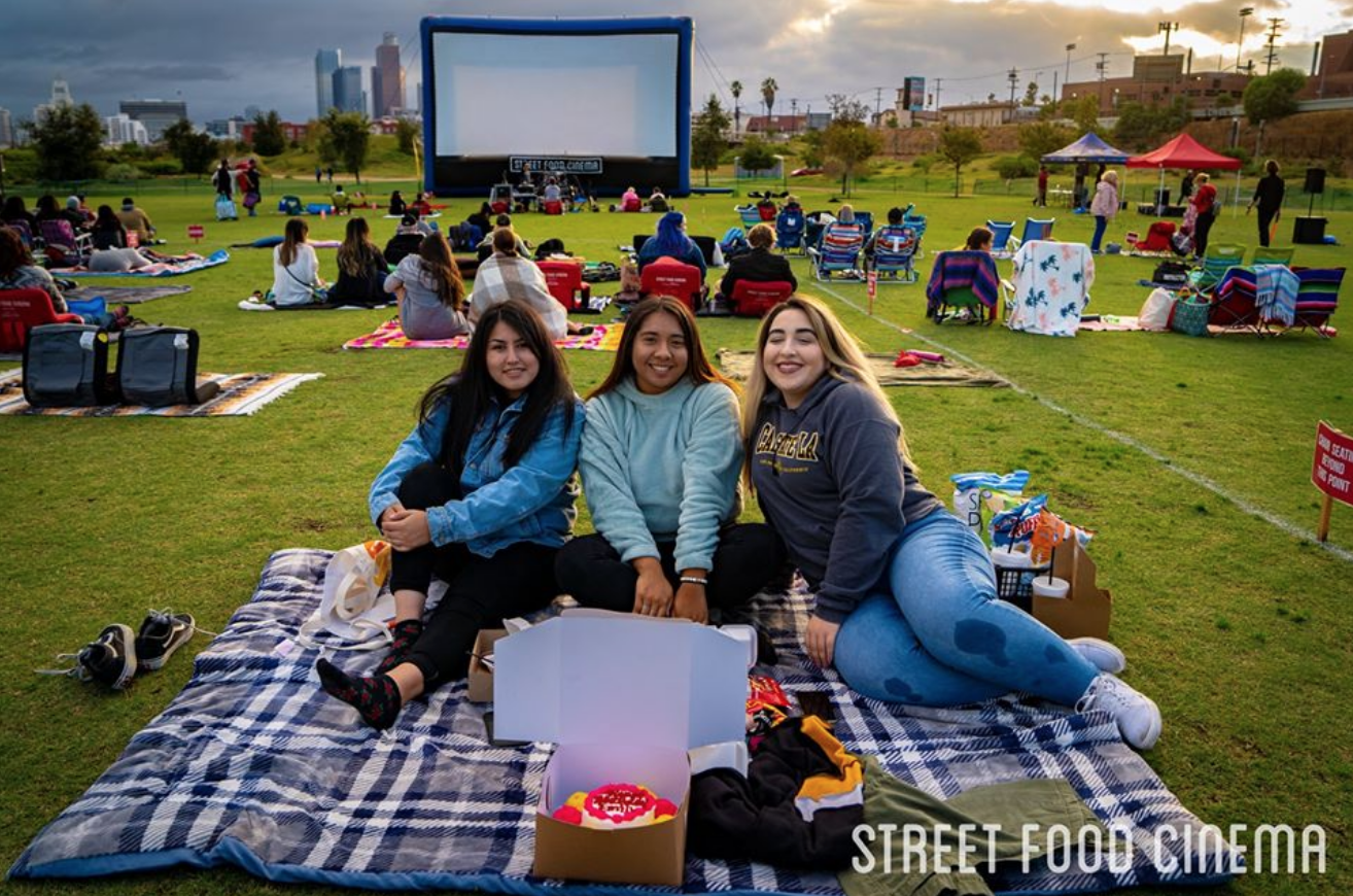 A group of young girls gather for a picture in front of a large screen at the park for a Street Food Cinema event.