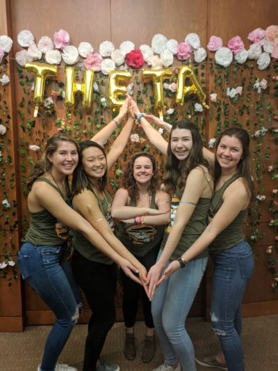 Megan and four other sorority women stand in front of the word Theta with their hands joining to form a kite shape.