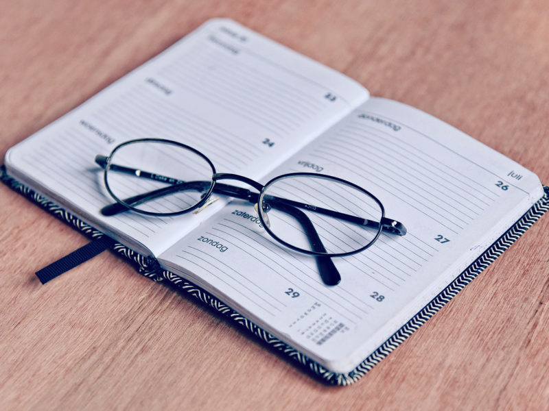 A pair of reading glasses sits atop a schedule planner notebook - making a routine when campus and businesses are closed is difficult but worth it.
