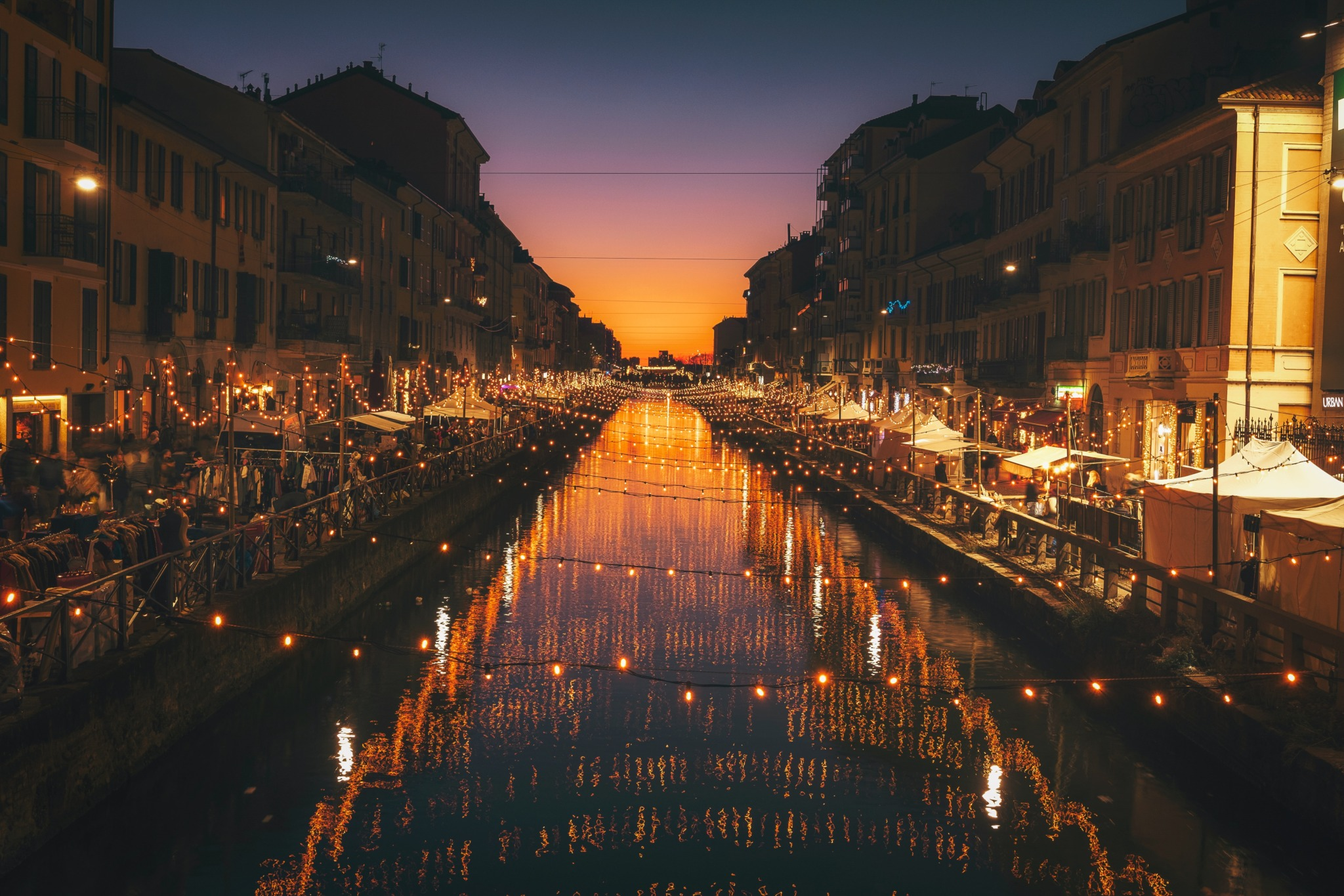 photo of a river in Milan at night with lights strung over it