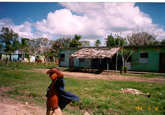 photo of a child standing in front of a house in Batey, Dominican Republic