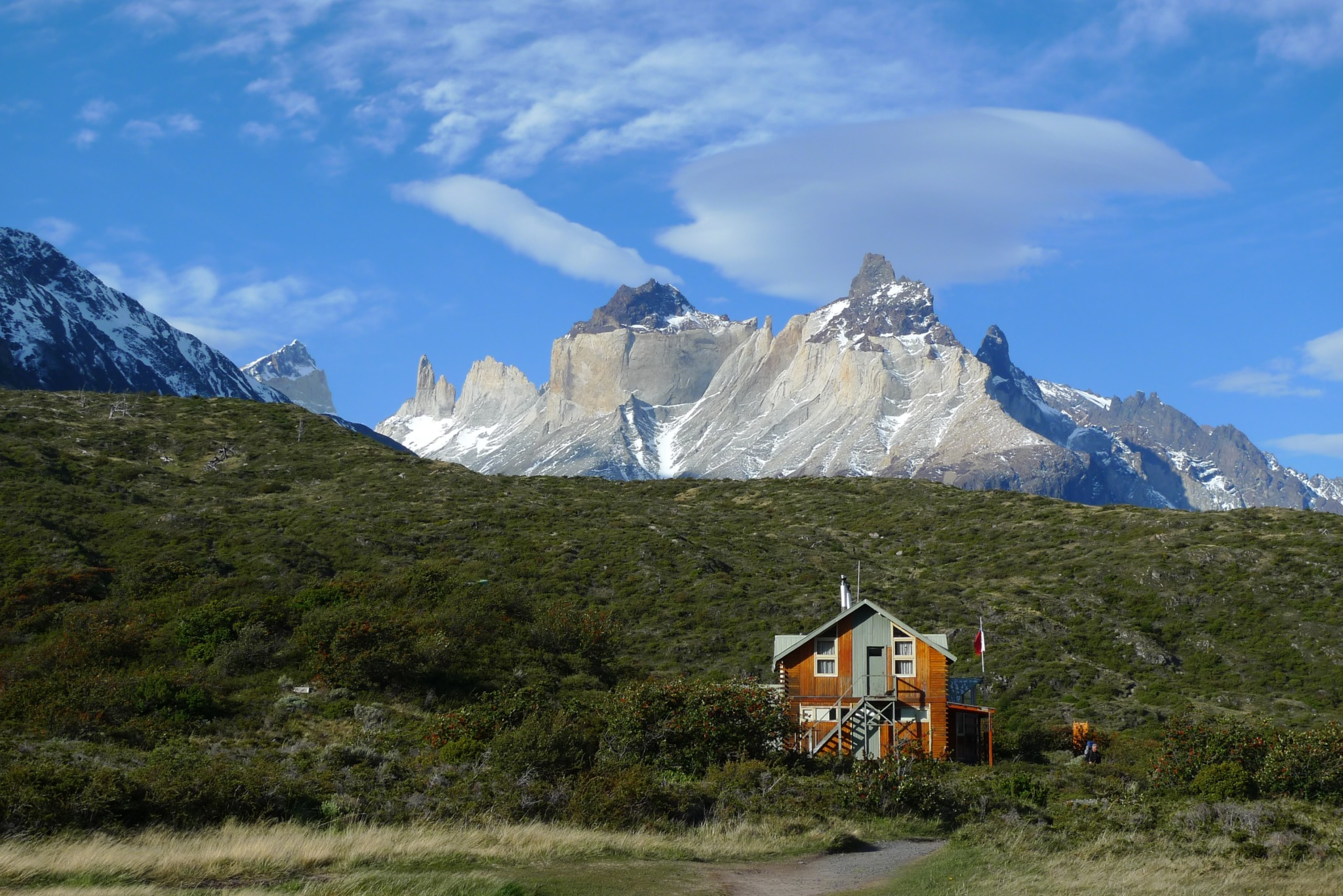 photo of Patagonia of a house in a green hillside standing before tall mountains