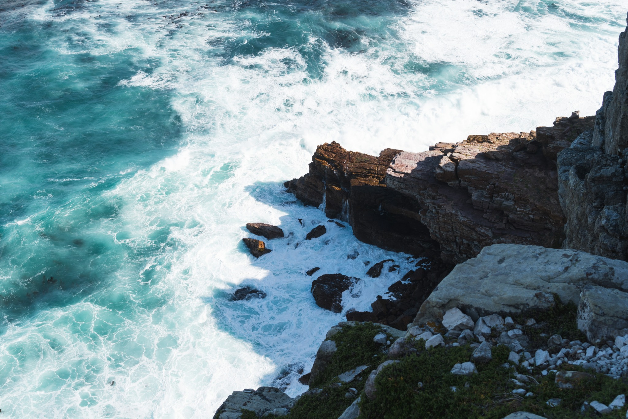 photo overlooking the Cape of Good Hope in South Africa with the ocean water crashing against the jagged rocks.
