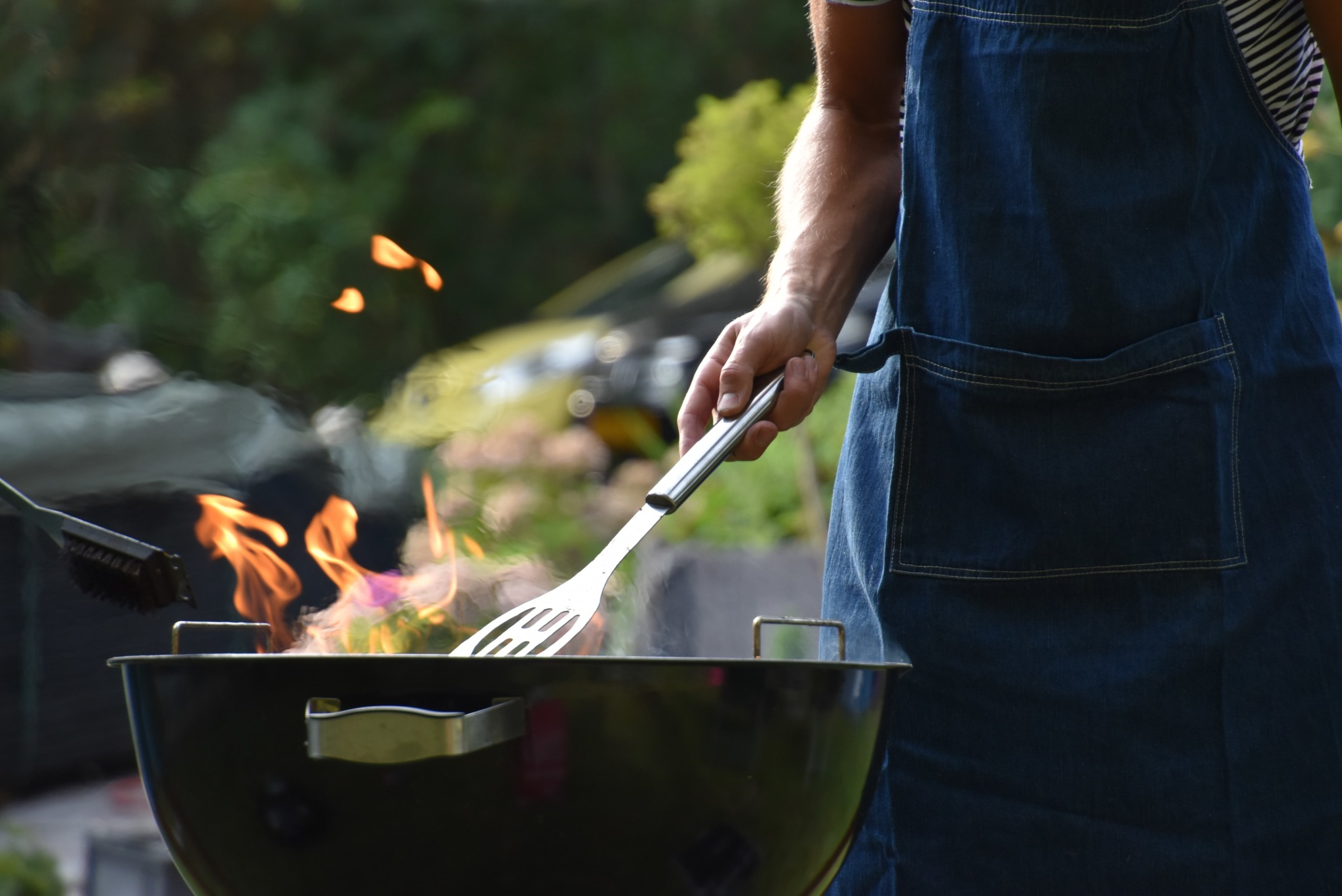 man places spatula on blazing grill outside