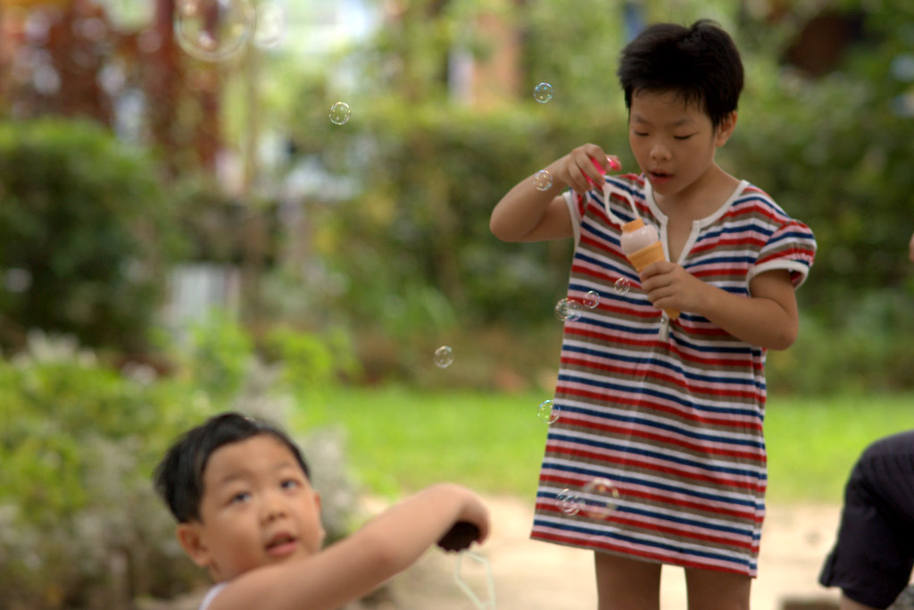 two kids play with bubbles outside