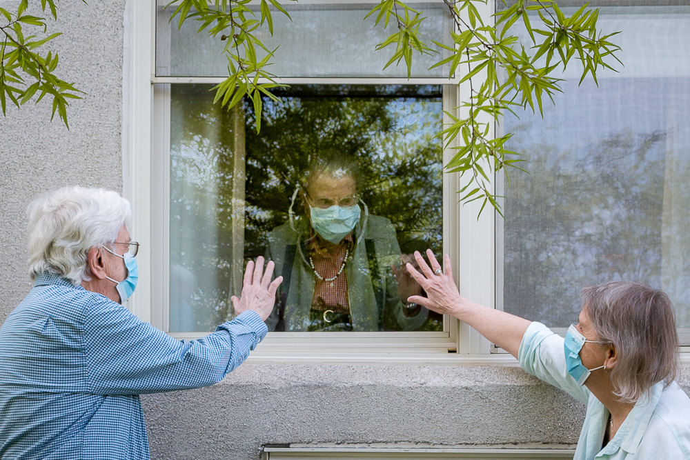 older aged people visit each other through a window during the COVID pandemic