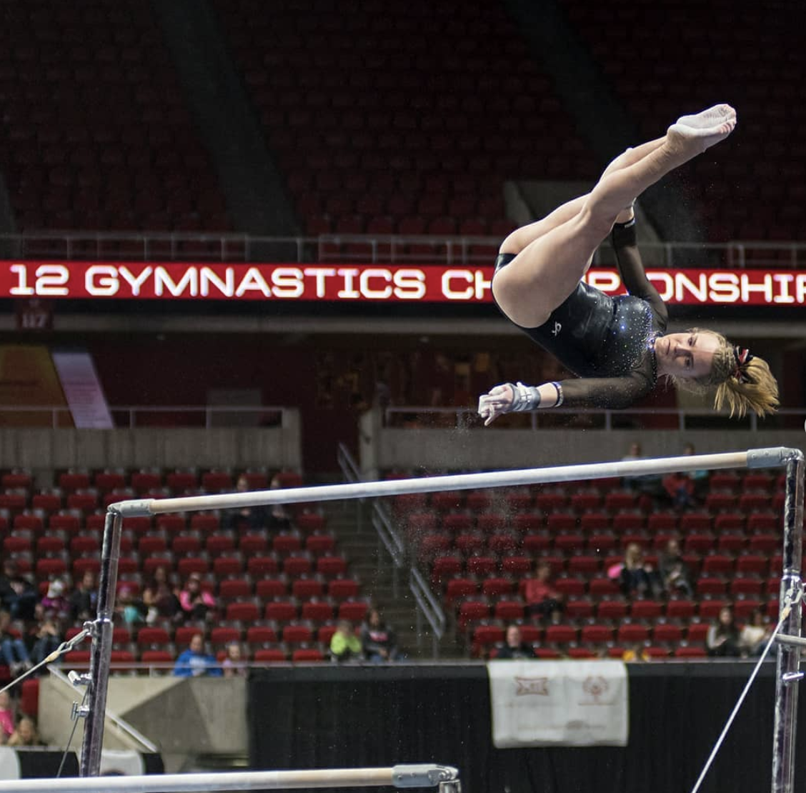 a gymnast flipping on the uneven bars