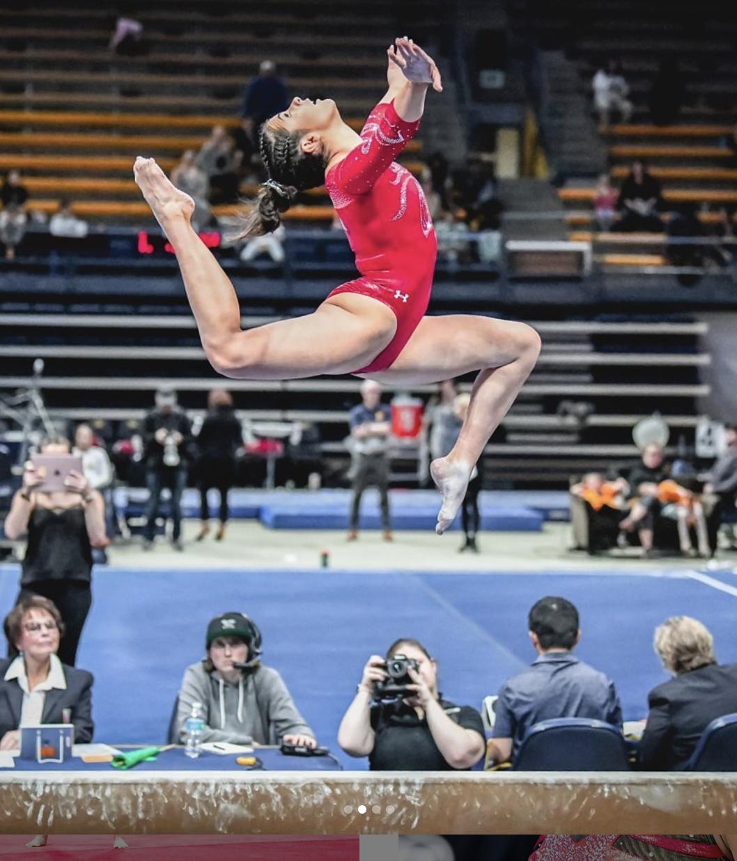 a gymnast jumping on the balance beam