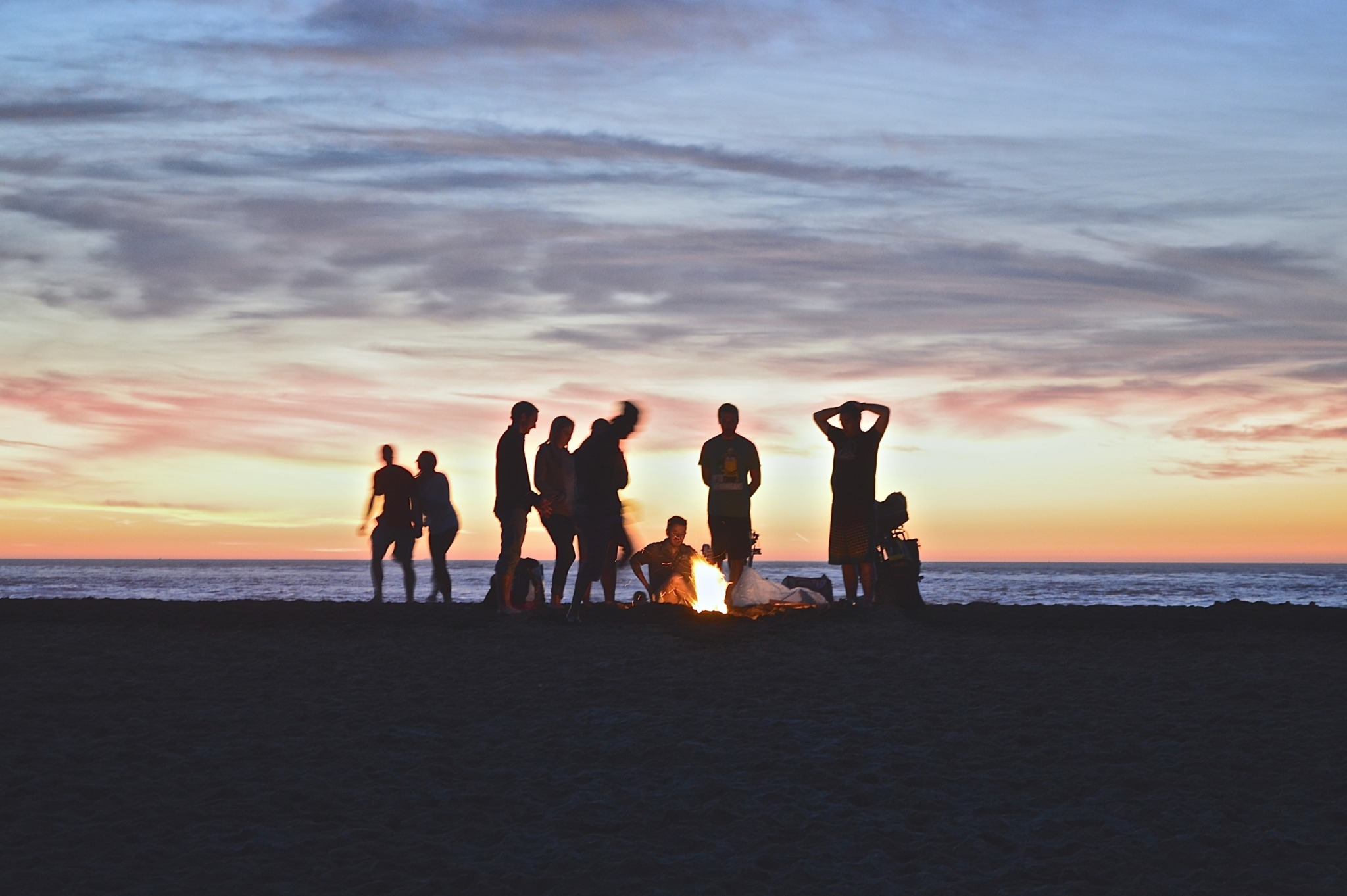 people at a beach bonfire