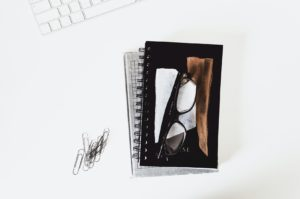 glasses on top of notebooks and books