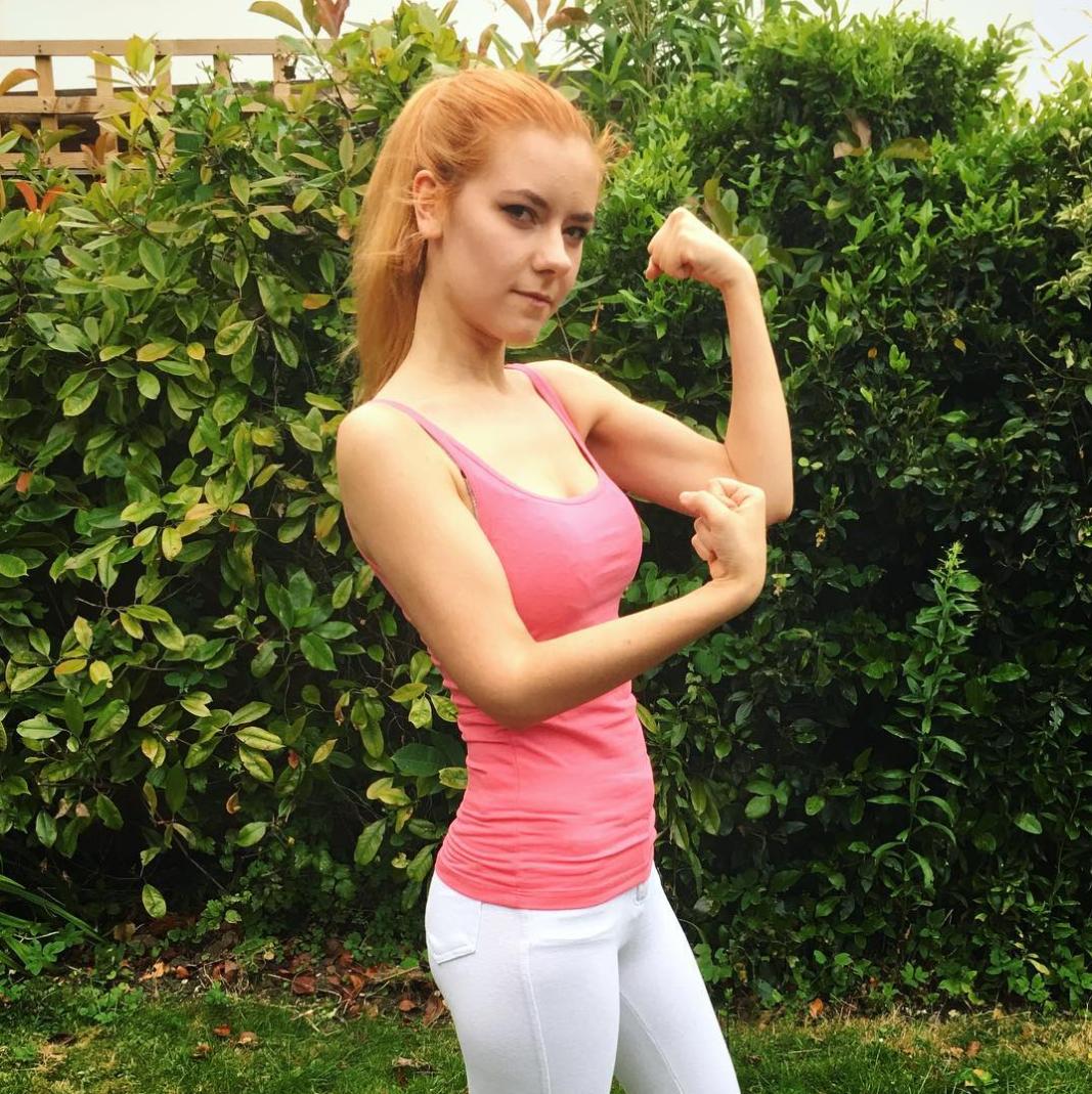 A ginger girl wearing a pink tank top flexes.
