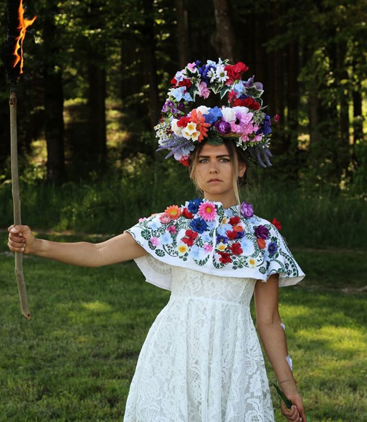 A girl burns a stick dressed in a flowery outfit.
