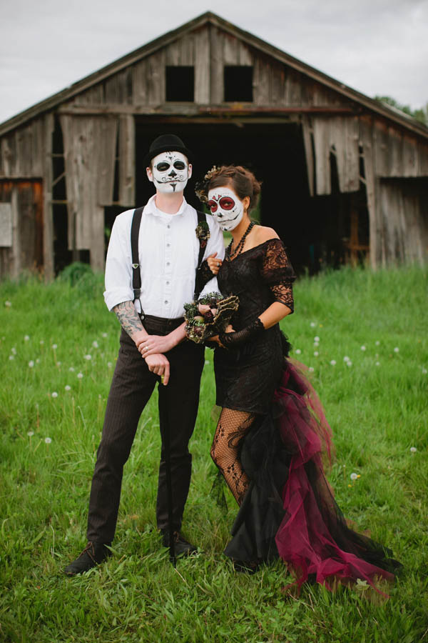 couple in day of the dead makeup in front of a barn